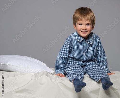 Little boy wearing blue pyjamas in bed