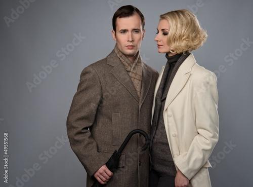 Elegant couple with umbrella isolated on grey