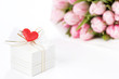 Gift box decorated with heart with tulips on the background
