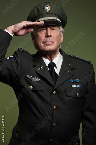 US military general wearing cap. Salutation. Studio portrait.
