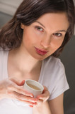 Macro view of a beautiful young woman holding a cup of tea or co