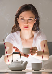 Young woman sitting in meditation pose in front of tea set and a