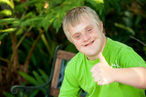 Cute handicapped boy showing thumbs up outdoors. - Fine Art prints