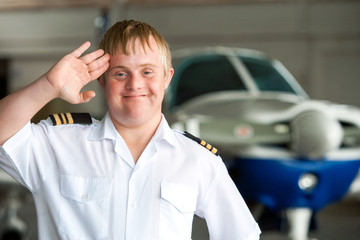Portrait of young pilot with down syndrome in hangar.
