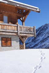 Chalet with prints in the snow