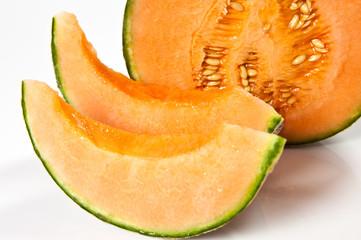 melone aperto e fette su sfondo bianco
