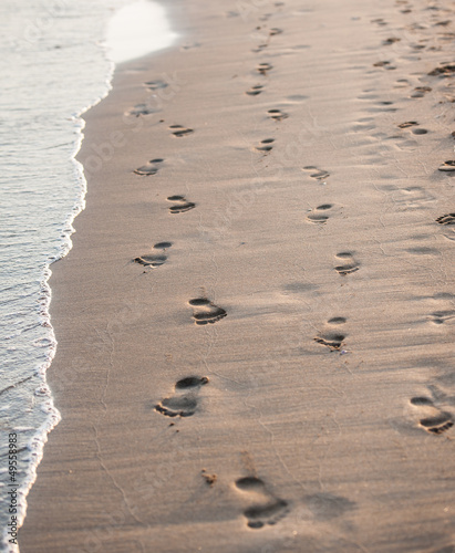 Footsteps of couple on the beach by the sea in summer