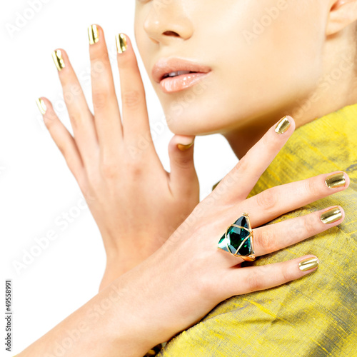 Women hands with golden nails and precious stone emerald