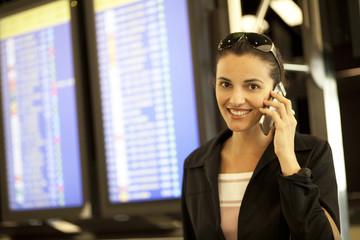 Frau telefoniert am Flughafen