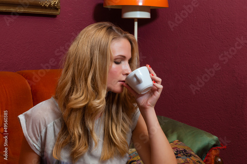 Young woman drinking a coffee or cappuccino