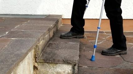 Person mit Krücken beim Treppensteigen