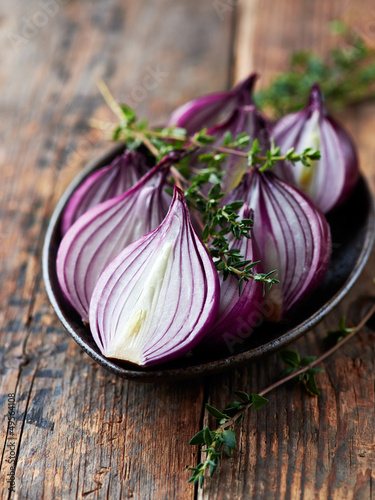 Halved red onions with thyme on a ceramic plate