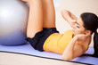 Woman doing abdominal muscles with a fitness ball