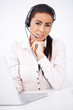 Business woman with headset sitting in front of laptop