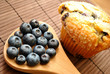 Muffin Next to Fresh Blueberries on a Spoon