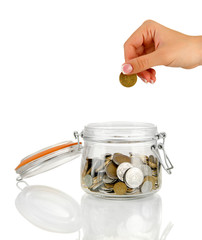 Saving, female hand putting a coin into glass bottle, isolated