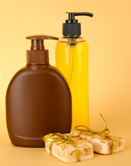 Liquid and hand-made soaps on beige background