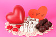 Sweet cookies with hearts and valentine card on pink background