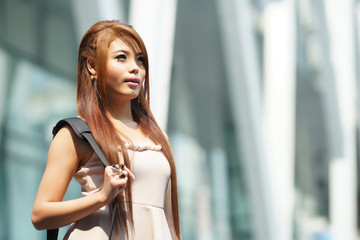 Beautiful business woman walking outside her office with briefca
