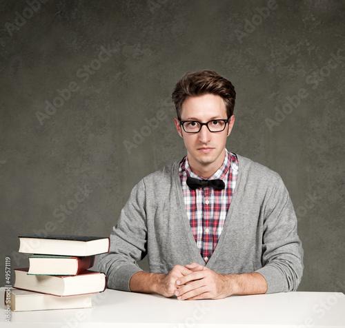 Student mit Büchern sitzt vor einer Tafel