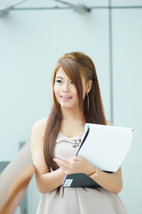 Portrait of young business woman standing near window in modern