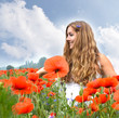 Sommer-Glück: Junge, blonde Frau in Klatschmohn-Wiese