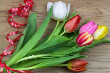 Tulpenstrauß mit Geschenkband auf Holz