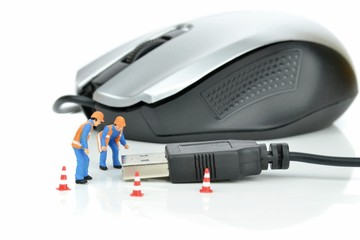 Mini workmen repairing a computer mouse