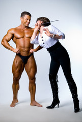 A woman with a pointer next to a bodybuilder