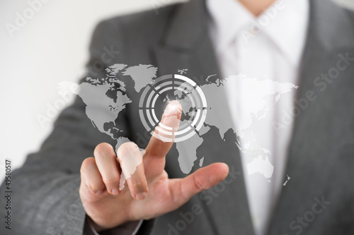 Business woman pointing her finger on virtual button on world ma