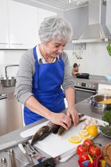 Ältere Frau bereitet Fisch zu - Hecht und Barsch
