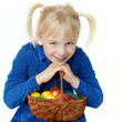 Cute blonde child is happy to find a lot of Easter eggs