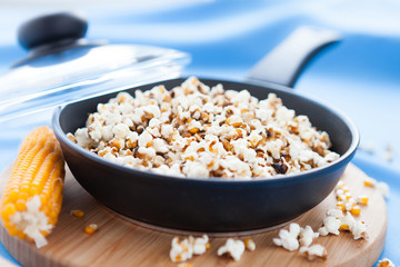 Popcorn cooked in a frying pan and ear of maize