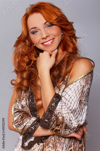 Smiling redhead woman is posing on a camera