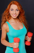 Woman posing with dumbbells on a dark background