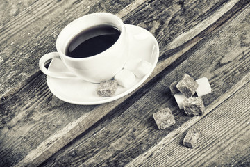 Black and white image of coffee cup and sugar