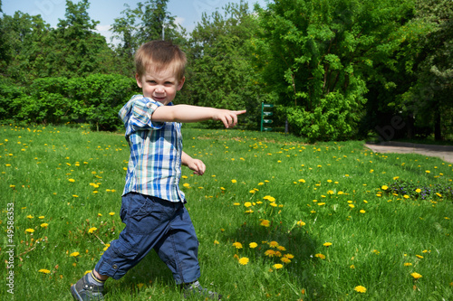 Little boy goes on meadow and indicates direction