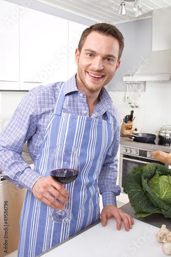 Lachender Mann in der Küche trinkt Rotwein