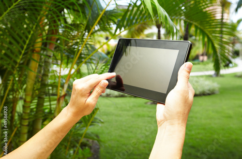 Hands with tablet computer in tropical garden.