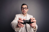 Young nerd with eyeglasses holding joystick and playing games
