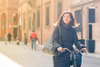 Woman riding bicycle in Bologna, Italy.