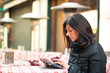 Woman using tablet outdoors sit in a bar. Shallow depth of field