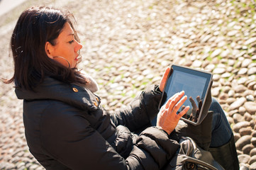 Woman using tablet to surf the web outdoors.