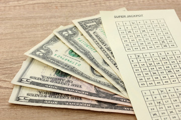 Lottery ticket and money, on wooden background