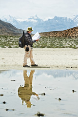 Tourist hiker with compass and map in mountains