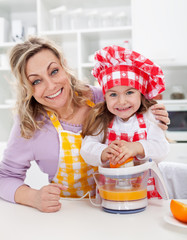 Happy woman and child making fresh orange juice