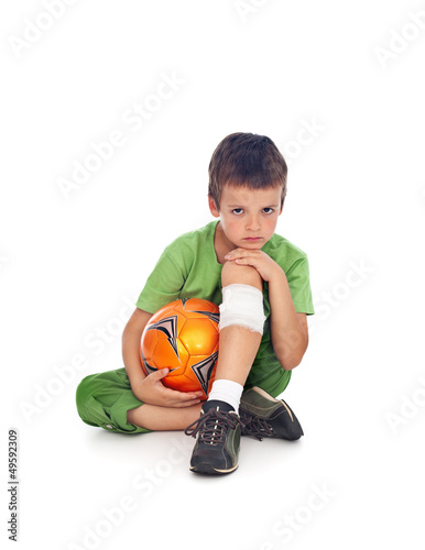 Boy with injured leg and soccer ball