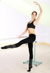 Pretty ballerina girl standing by bar in dance studio
