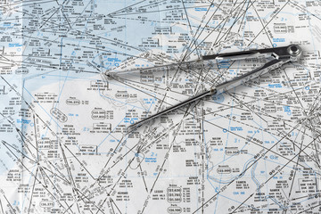 A pair of compasses on an aeronautical navigational chart