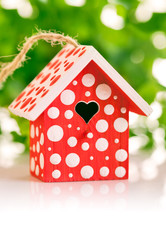 red birdhouse in white polka dot on green background